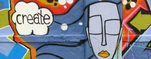 """think box says """"create"""" graffiti features a gender-neutral face, with eyes closed, and yellow lips."""