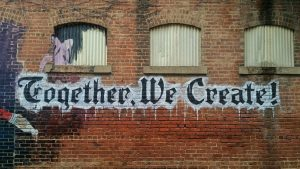"""""""Together, We Create"""" written in graffiti on a brick wall"""