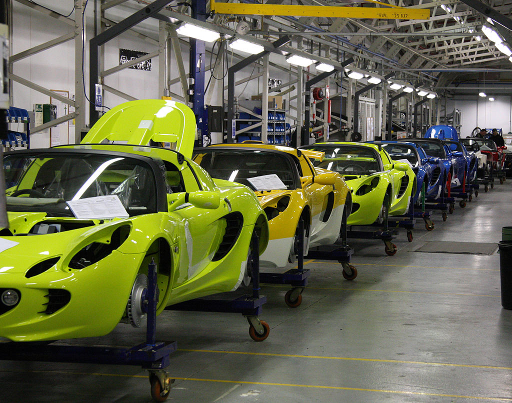 Image shows a long line of sports cars in a factory. The cars are not yet fully assembled.