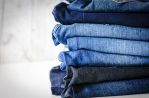 Image shows a pile of jeans of various shades of blue.