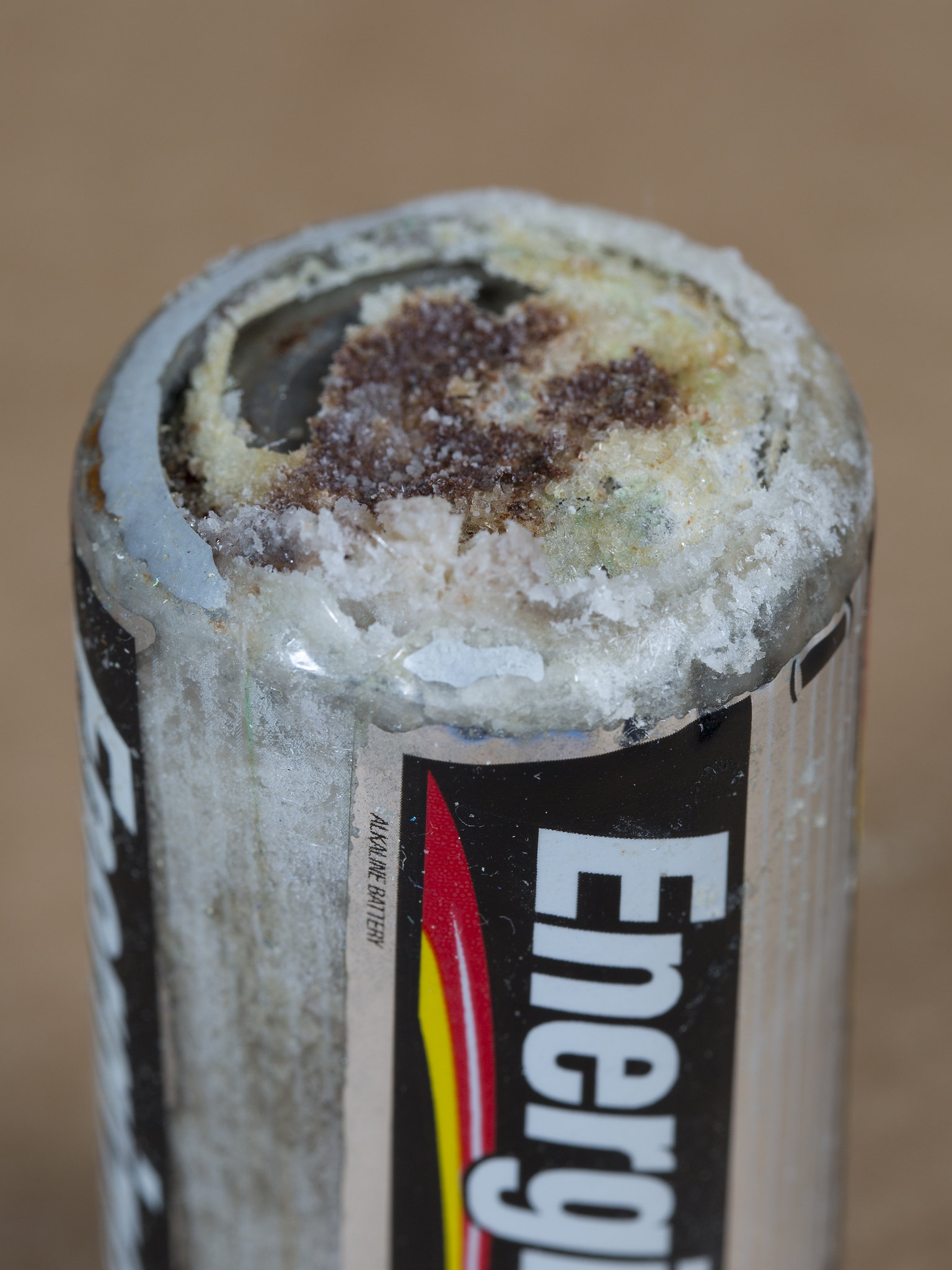 Image shows the end of a battery which has leaked its acidic contents. The leak looks like a thick crust of a whitish substance.