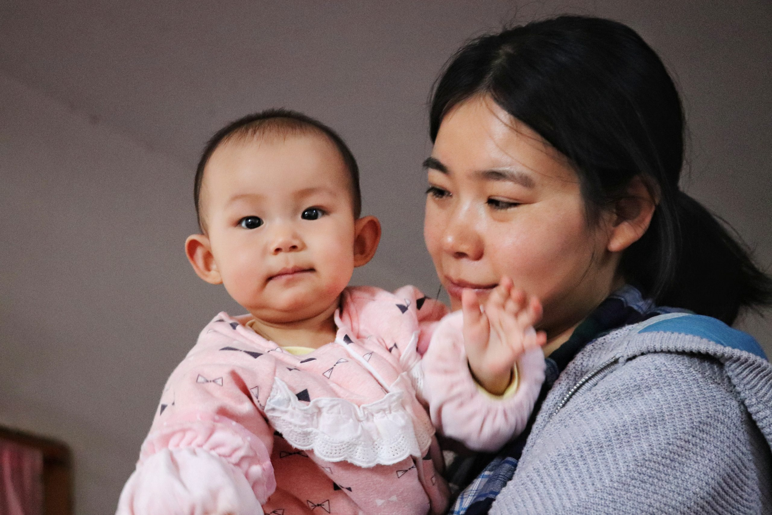Image shows a photo of a mother holding her baby girl.