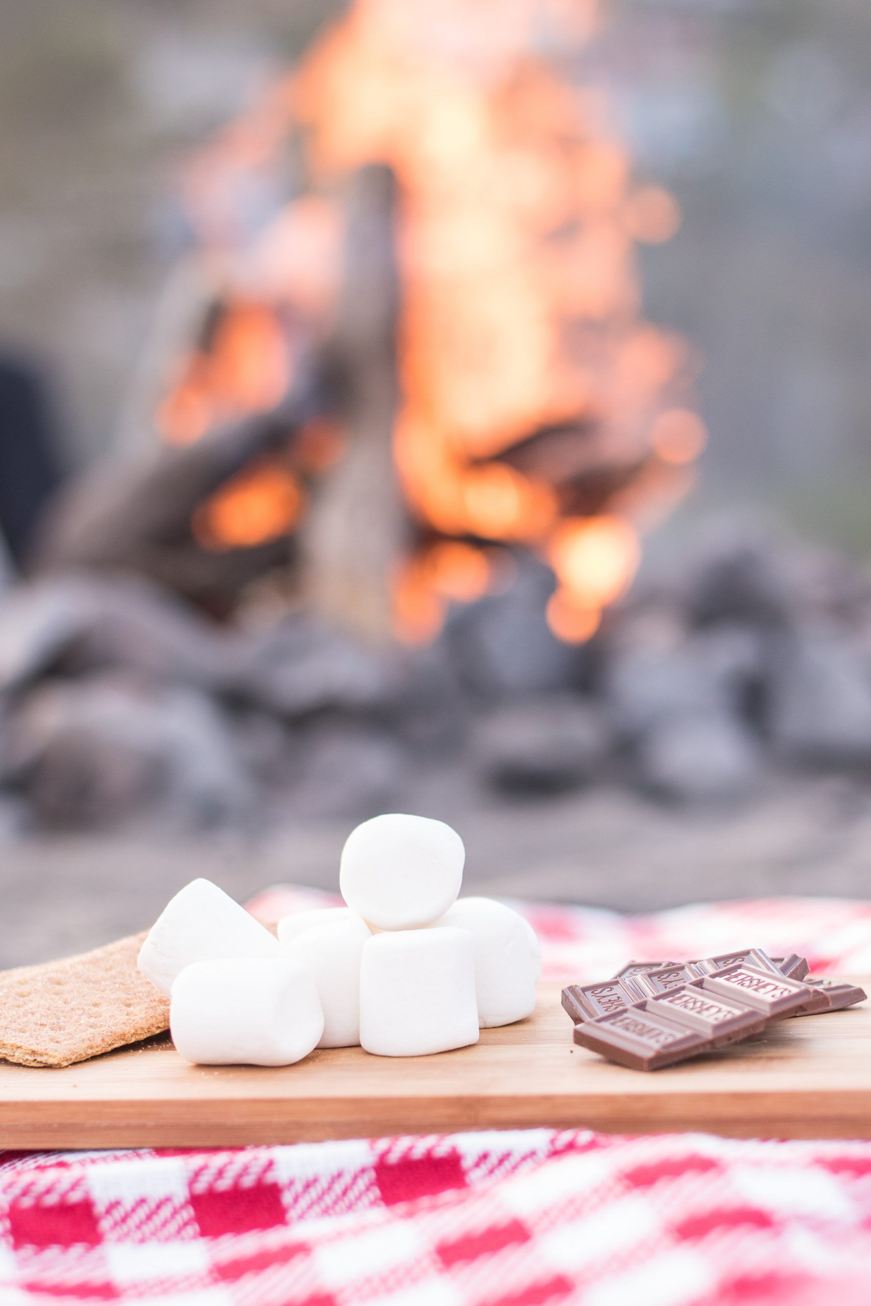Image shows a photo of the ingredients for smores sitting on a table. In the background, a campfire is burning.