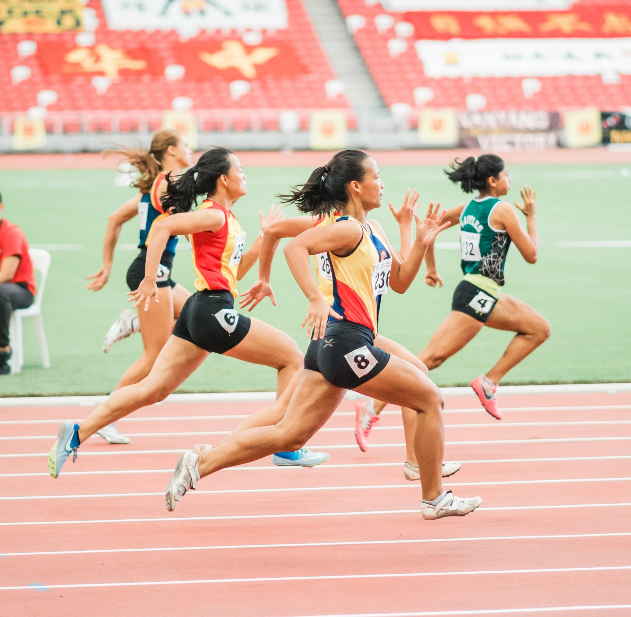 Image shows a photo of women in a short distance running race on a track.