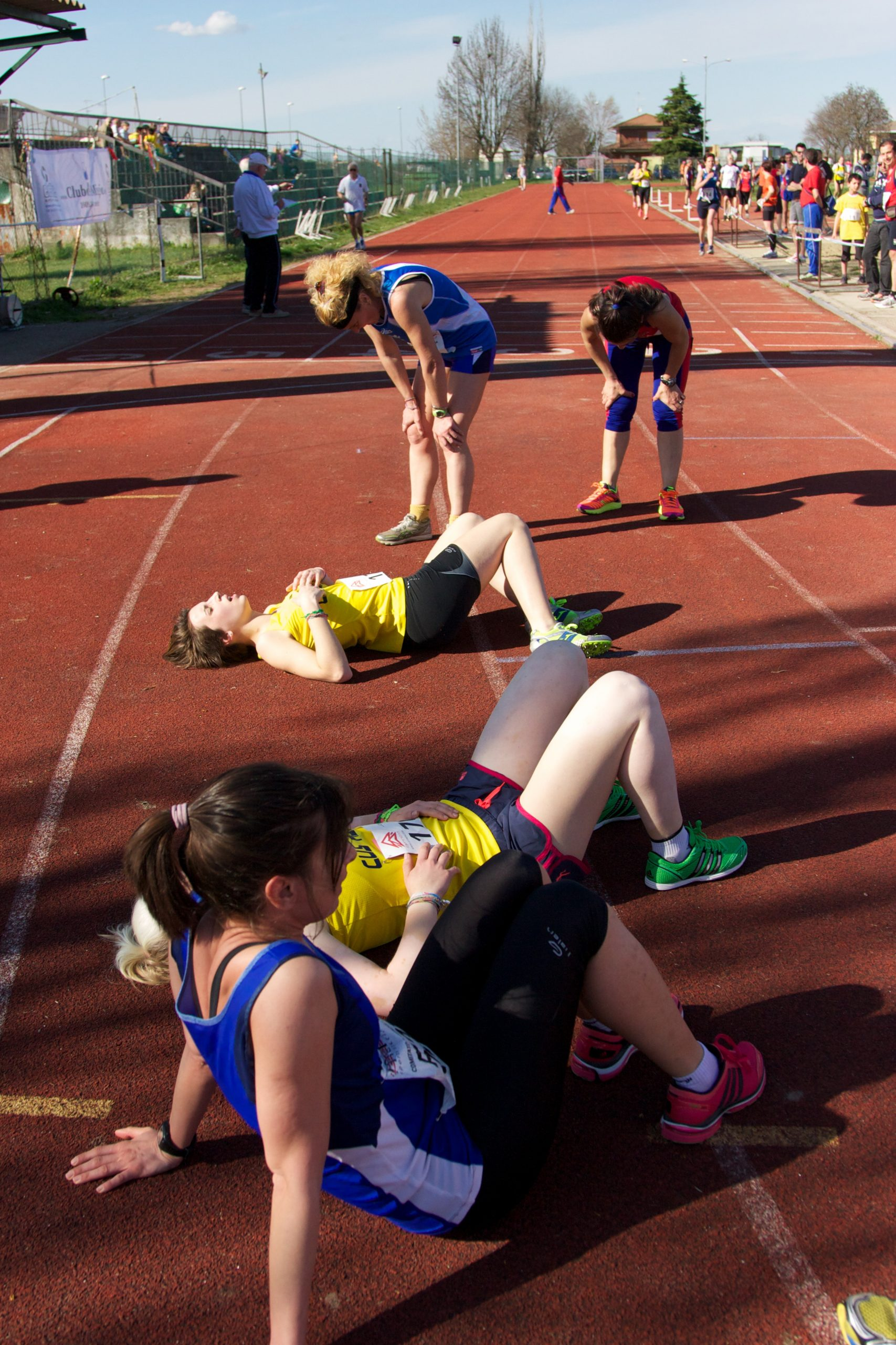 Image shows female track and field runners resting after a race. Three women are resting on the ground and two are leaning over with their hands on their knees, catching their breathe.