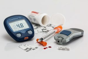 Image shows equipment related to treatment of diabetes. Blood sugar monitor, insulin, hypodermic needle, and a prescription bottle.