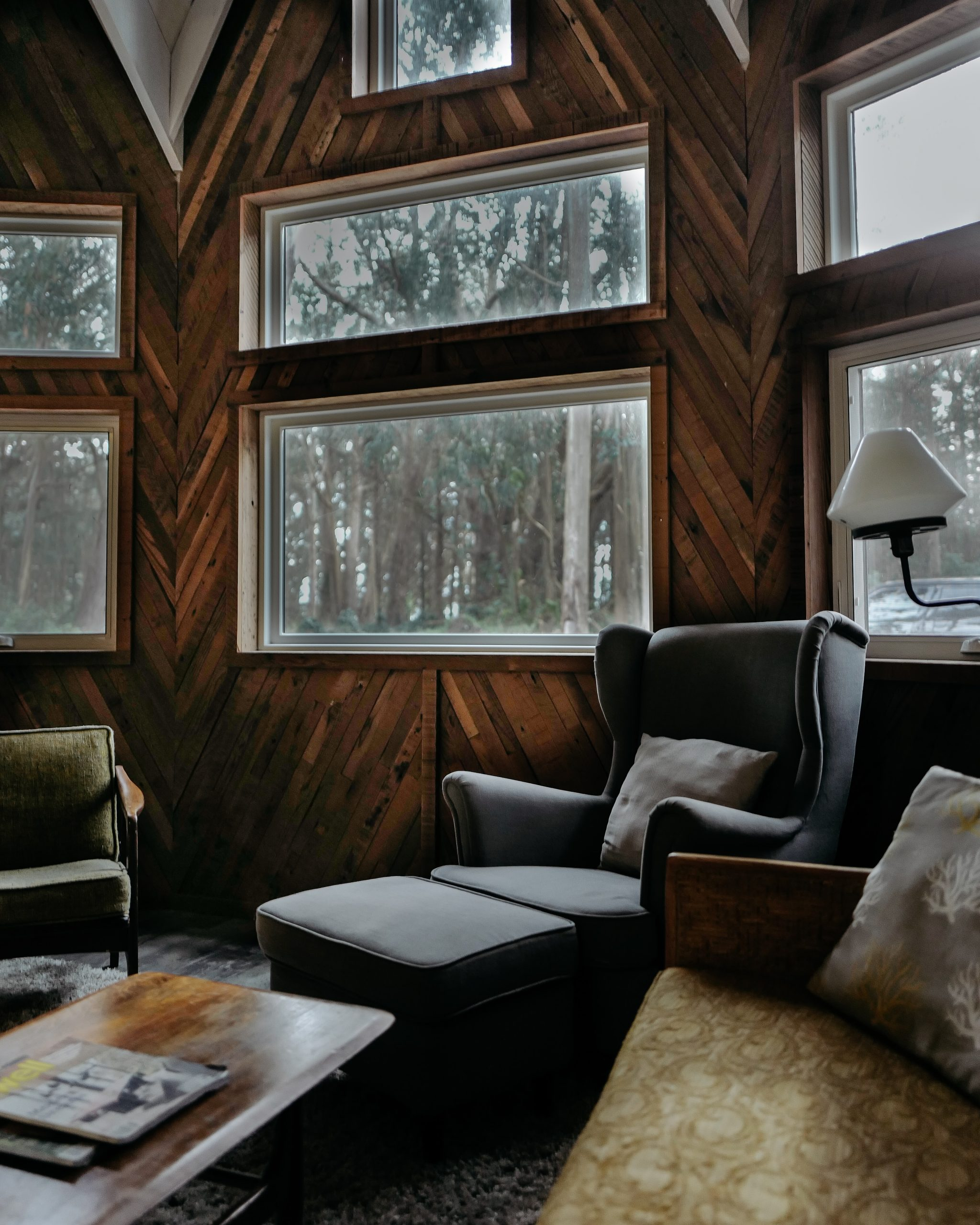 Image shows a photo of a living room with large windows. There is a leather armchair, coffee table, lamp and books. The walls have wood panelling.
