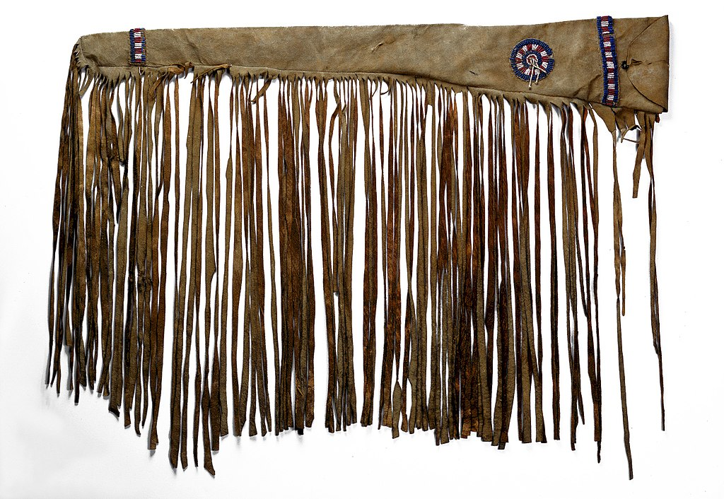 Image shows a plains first nations rifle guncase made from the hide of a buffalo. It has beadwork and fringes.