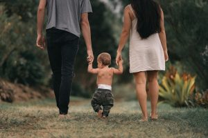 Image shows a man and woman holding hands with a toddler between them. All three are walking down a grassy path in their bare feet.