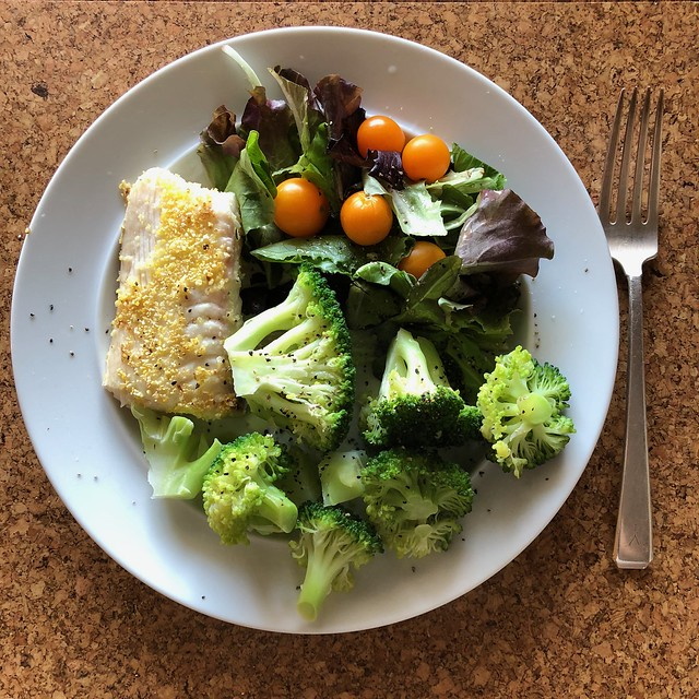 Image shows a plate of food containing a salad, fish and broccoli.